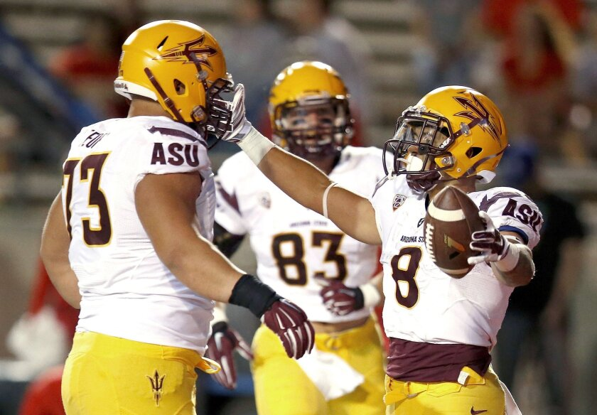 Arizona State's D.J. Foster (8) celebrates his touchdown run against New Mexico with teammates Vi Teofilo (73) and Kody Kohl (83) during the second half of an NCAA college football game Saturday, Sept. 6, 2014, in Albuquerque, N.M.  Arizona State defeated New Mexico 58-23. (AP Photo/Ross D. Frankli