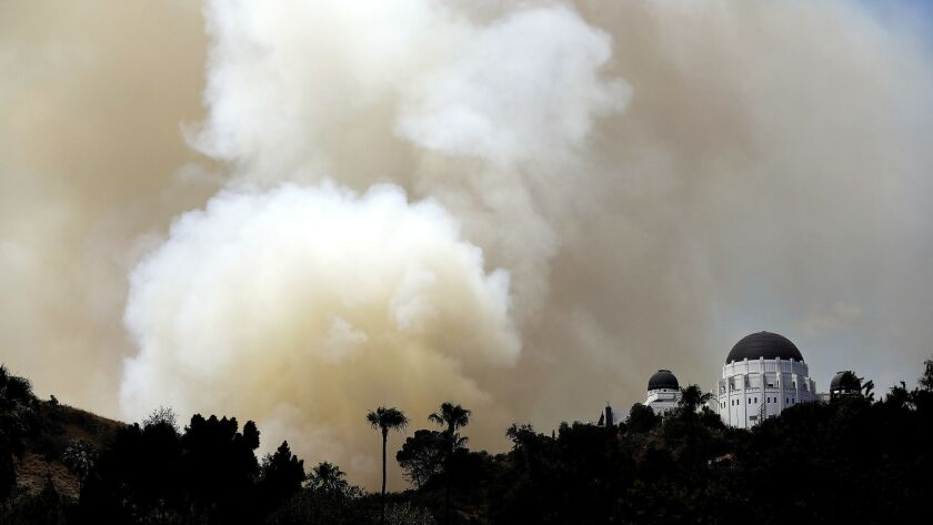LOS ANGELES-CA-JULY 10, 2018: Smoke billows from a brush fire in Griffith Park near Griffith Observa