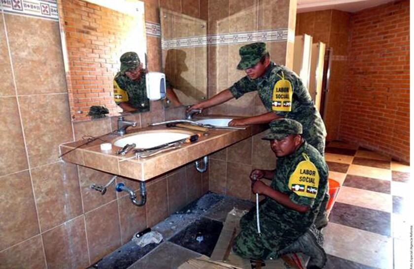 Dos militares realizando trabajo social.