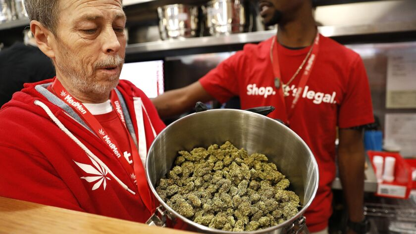 On the first day of recreational marijuana sales, Jeff Cosper shows the inside of a stainless steel pot filled with marijuana for sale at MedMen in West Hollywood.