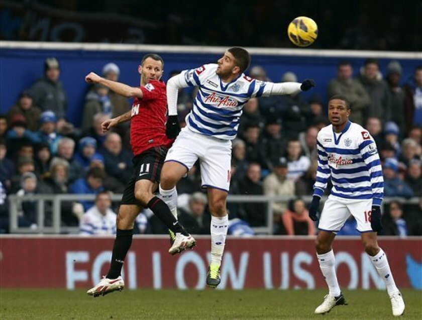 Manchester United's Ryan Giggs, left, fights for the ball with Queens Park Rangers' Adel Taarabt, center, during a English Premier League soccer match at Loftus Road ground in London, Saturday, Feb. 23, 2013. Manchester United won the match 2-0. (AP Photo/Lefteris Pitarakis)