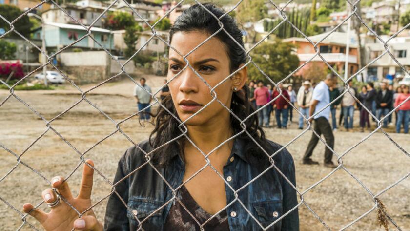 Luciana (Danay García) observa estoicamente a un hombre que se sacrifica él mismo ante los zombies en la película 'The Walking Dead'.