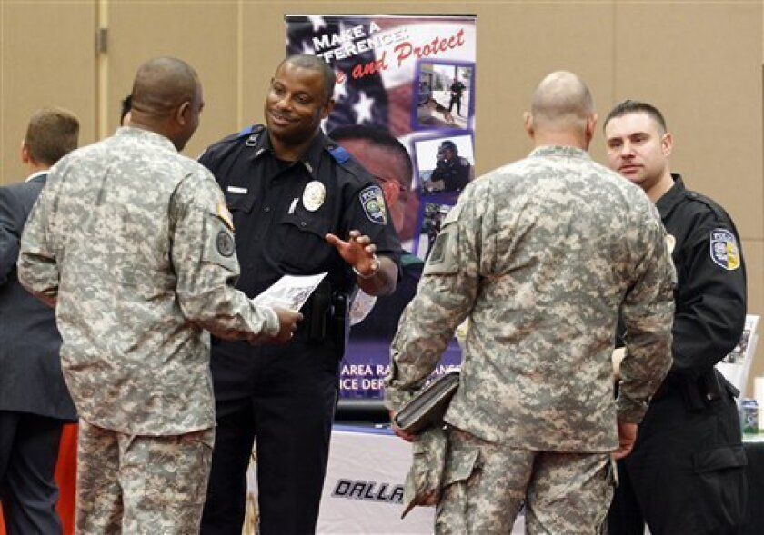 FILE - In this July 19, 2012, file photo, military job seekers line up to speak to law enforcement recruiters during a job fair Thursday, July 19, 2012, in Irving, Texas. Even as it faces budget cuts and forced employee furloughs, the Pentagon is spending nearly a $1 billion a year on a program that sends unemployment checks to former troops who left the military voluntarily. But eligibility for the military compensation requires only that a person served in uniform and was honorably discharged.
