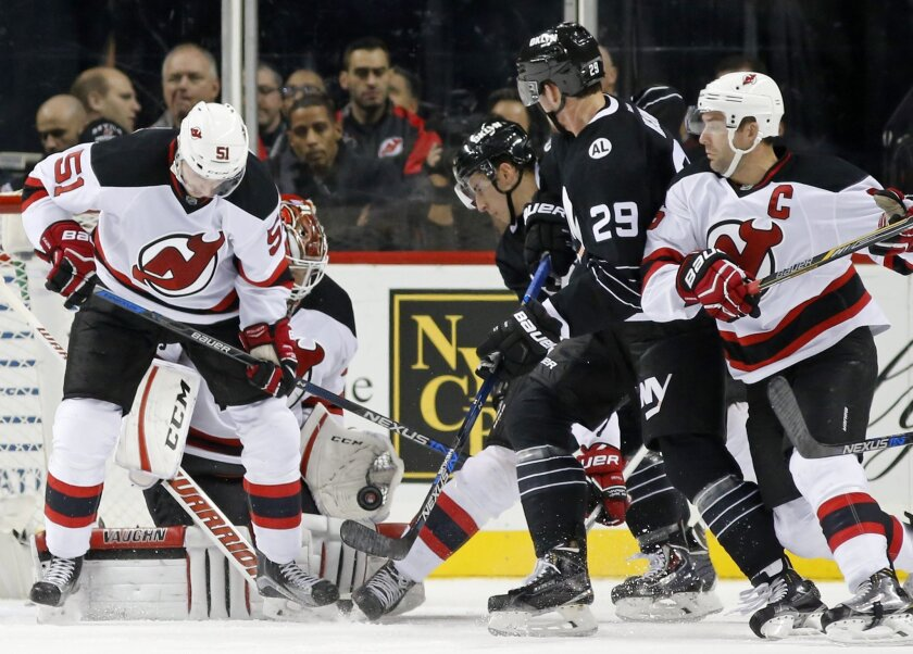 New Jersey Devils goalie Cory Schneider, second from left, makes a glove save as center Sergey Kalinin (51), of Russia, defends with New York Islanders center Brock Nelson (29) and a teammate threatening near the crease during the first period of an NHL hockey game in New York, Tuesday, Nov. 3, 201