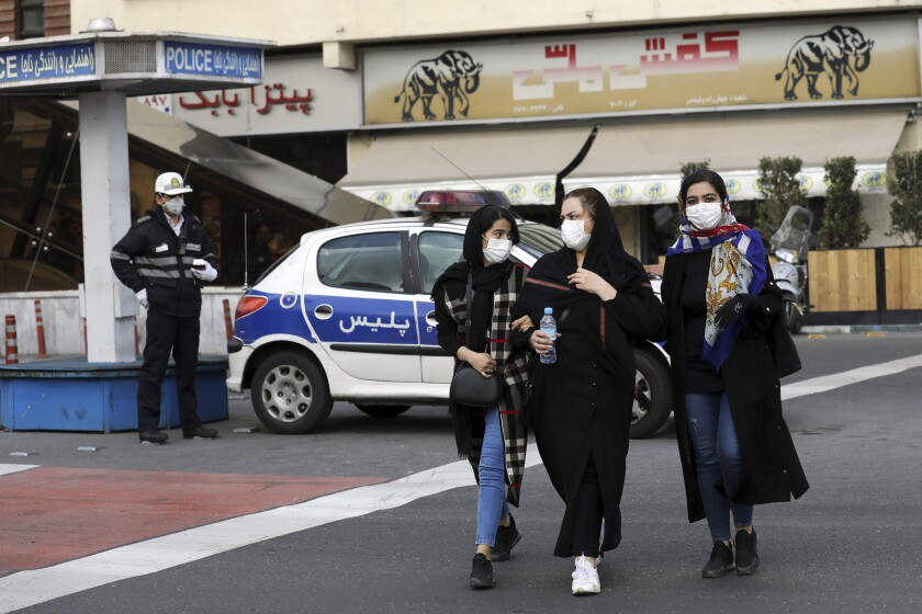A policeman and pedestrians wear masks to help guard against the coronavirus on Feb. 23 in downtown Tehran.