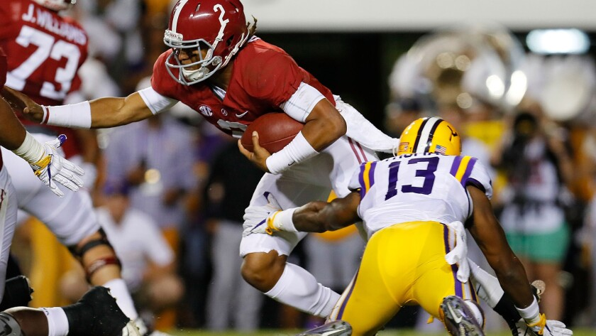 Alabama quarterback Jalen Hurts attempts to break a tackle by LSU's Dwayne Thomas during their SEC game Saturday.