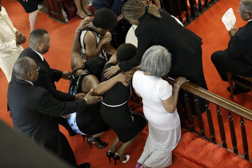 Ushers come to the aid of a woman who collapsed while praying at the Emanuel African Methodist Episcopal Church in Charleston, S.C., on Sunday. The day marked the reopening of the church after Wednesday night's deadly shootings there.