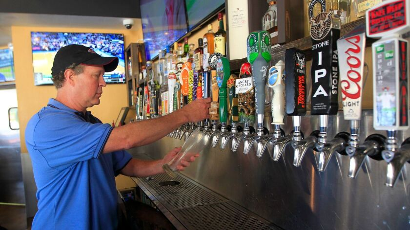 SAN DIEGO, CA - APRIL 5, 2017 - Mike Pasulka, owner of Players Sports Grill in Poway pours a beer f