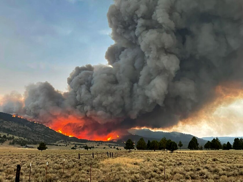 A large cloud of smoke rises from a fire behind a hill