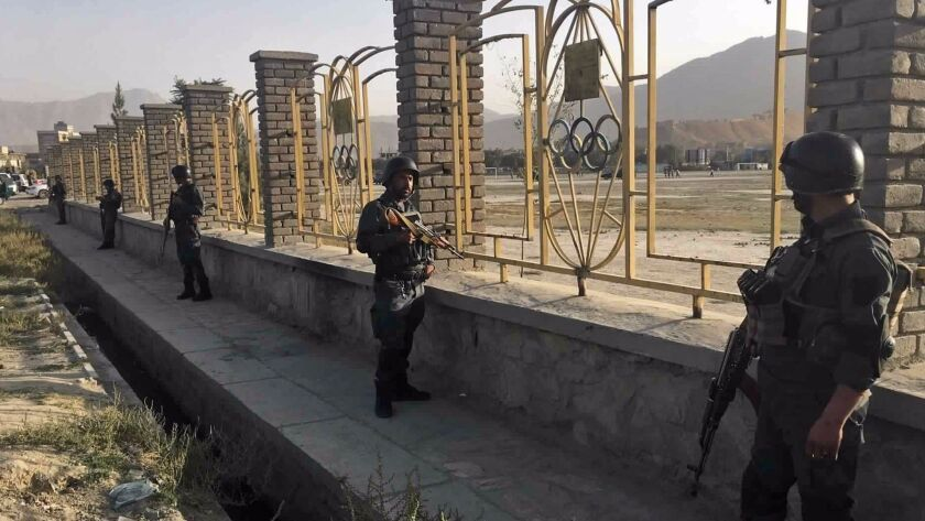 Afghan security police stand guard near the site of a deadly suicide attack outside a cricket stadiu