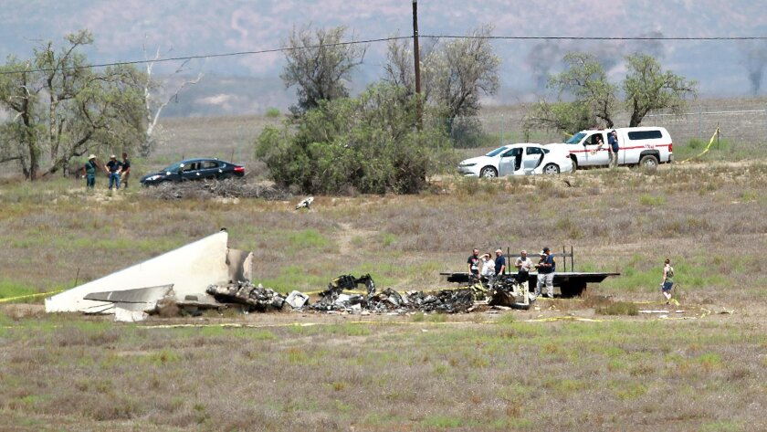 People described as family members survey the aftermath scene of Sunday's mid-air collision on Monday around midday.