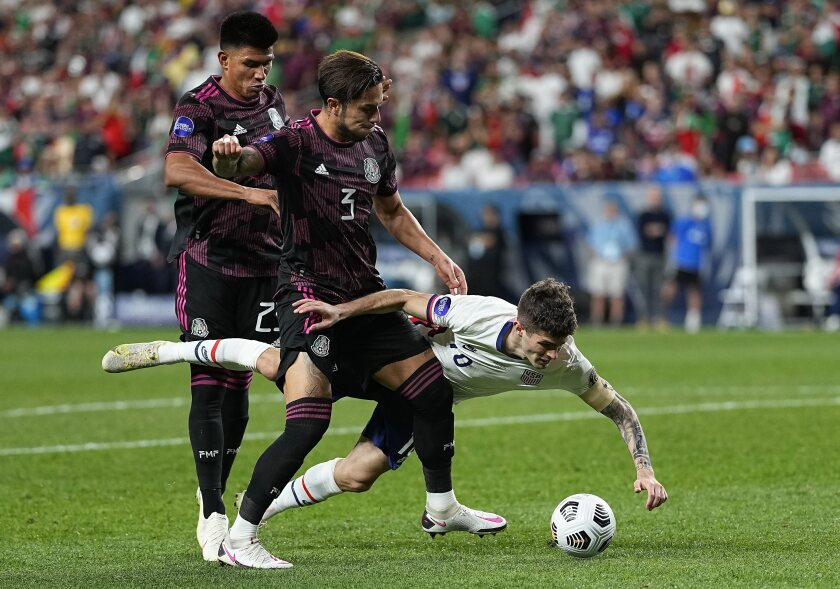 The United States' Christian Pulisic (10) is knocked down by Mexico's Jesús Gallardo (23) and Carlos Salcedo (3).