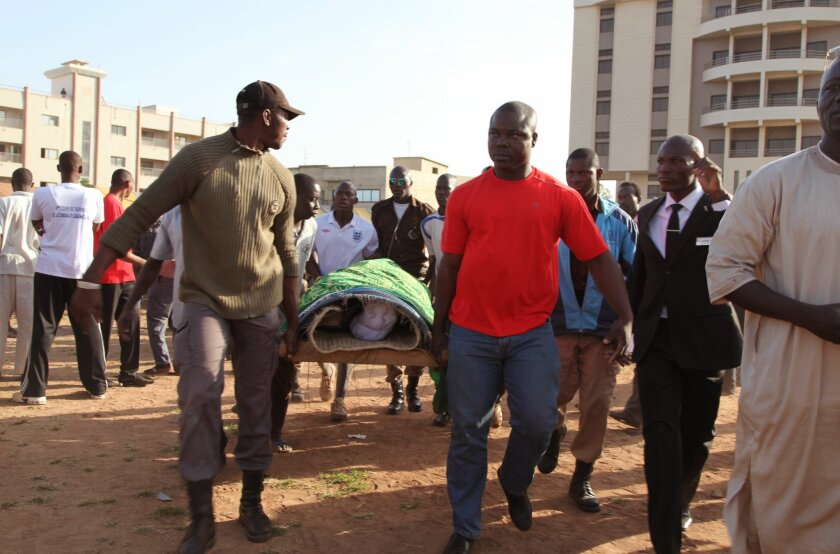 People carry the remains of a person that was slain by gunmen during the recent attacks on the Radisson Blu hotel, during a funeral in Bamako, Mali, Wednesday, Nov. 25, 2015. Islamic extremists armed with guns and grenades stormed the luxury Radisson Blu hotel in Mali's capital on Friday, Nov. 20, 2015. (AP Photo/Baba Ahmed)