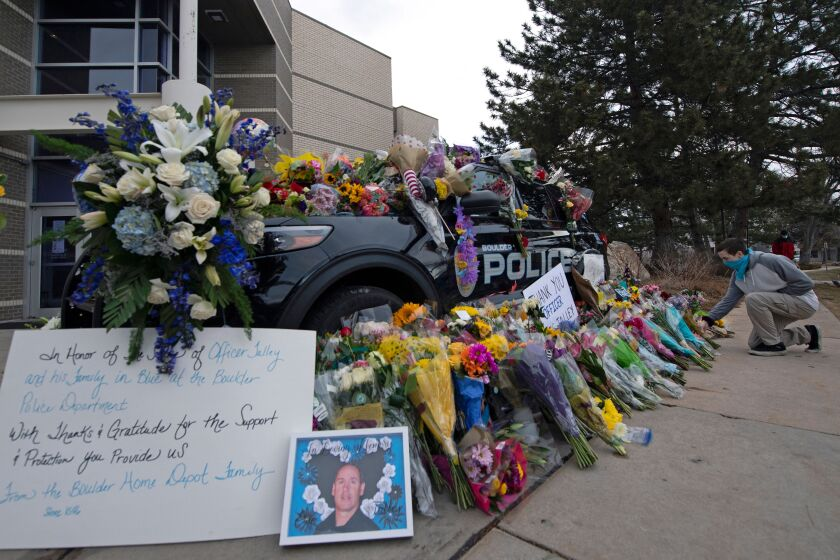 A man places flowers in honor of Boulder police officer Eric Talley, killed on March 23, 2021.
