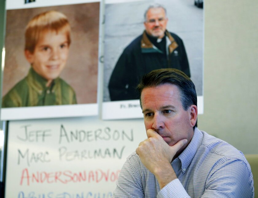 In this Sept. 26, 2016 file photo Eric Johnson pauses during a news conference in front of his childhood portrait and a portrait of former priest Father Bruce Wellems at an office in Chicago. Johnson was sexually abused by the priest as a child and was surprised when he saw photographs posted online of Wellems at Chicago Public Schools functions last year.