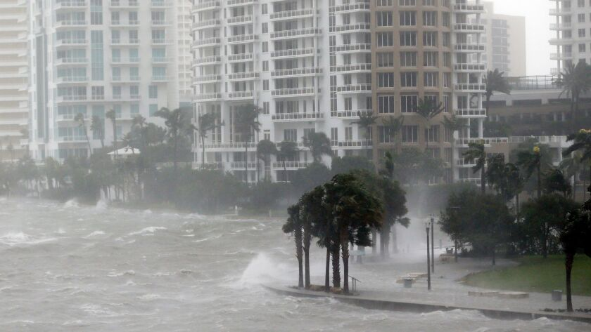 In this Sept. 10, 2017, photo, waves crash over a seawall at the mouth of the Miami River from Bisca