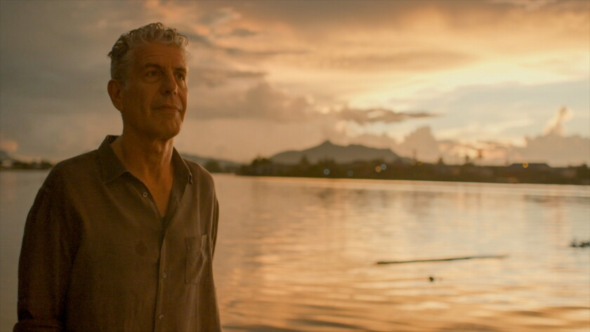 A man in a button-down shirt stands by a lake at sundown