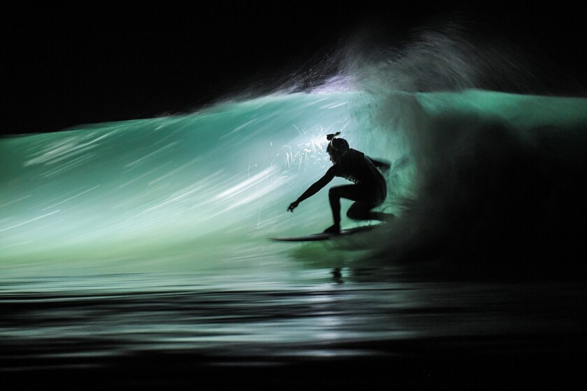 A surfer using a waterproof headlamp rides a wave at the Cap Frehel beach in Plevenon, France.
