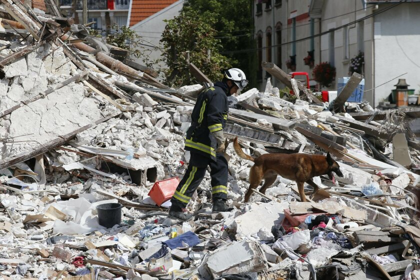 """A French fireman and his dog search in the rubble of a building after an explosion collapsed it, in Rosny-sous-Bois, outside Paris, Sunday, Aug. 31, 2014. French authorities say a four-story building in a northeastern Paris suburb has collapsed after an explosion, killing a child. More people are thought to underneath the rubble. Speaking on i-Tele, fire department spokesman Gabriel Plus said around 10 people were evacuated from the building in Rosny-sous-bois that occurred early Sunday morning. Plus said that around another 10 people could still be underneath the rubble, and emergency teams were working hard to rescue people who might be trapped. """"We could still find living victims in the hours to come,"""" he said. Interior Minister Bernard Cazeneuve has arrived at the scene, but couldn't confirm a theory that the explosion was caused by a gas leak. (AP Photo/Christophe Ena)"""