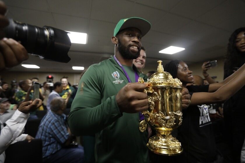South African Springbok rugby captain Siya Kolisi with the Web Ellis trophy arrives back on home soil at the O.R. Tambo Airport in Johannesburg Tuesday, Nov. 5, 2019. South Africa beat England in the Rugby World Cup final Saturday 32-12. (AP Photo/Themba Hadebe)