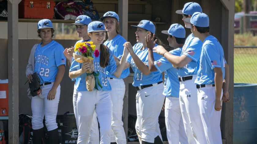 On Senior Day for the Pacific Ridge baseball team, Allison Wood receives high-fives from teammates, including Grace Li (11).