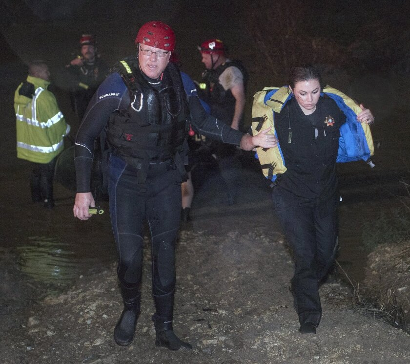 Firefighter Craig Bope assists Tarrant County Sheriff's Deputy Krystal Salazar after she was rescued from the raging waters of Deer Creek early Friday, Nov. 27, 2015, in Fort Worth, Texas. Salazar had gone into the water to attempt to rescue two other people that were swept away in the rushing waters, according to the Fort Worth Star-Telegram. The search continued for the missing people. (Glen E. Ellman/Star-Telegram via AP) MAGS OUT; (FORT WORTH WEEKLY, 360 WEST); INTERNET OUT; MANDATORY CREDIT