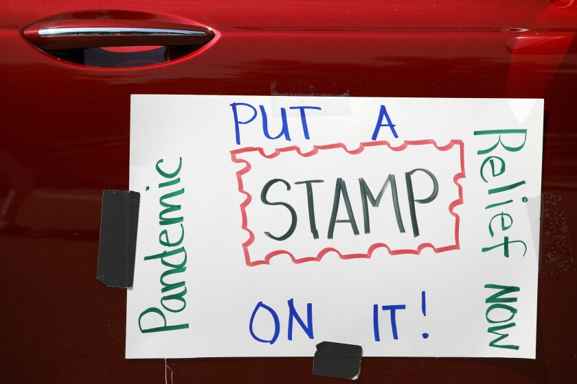 A car displays a sign asking Congress to approve emergency funding for the Postal Service
