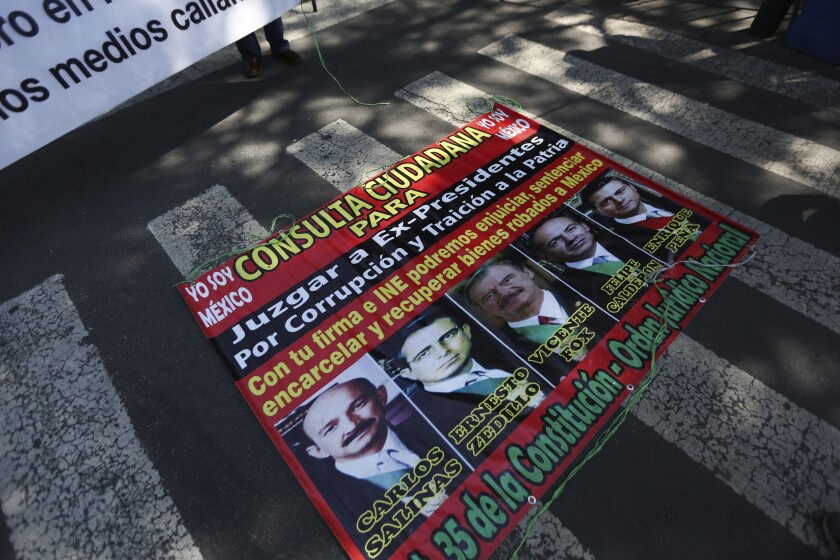 A poster with former Mexican presidents lays on the ground outside the Supreme Court during a demonstration by supporters of Mexico's current President Andres Manuel Lopez Obrador in Mexico City, Thursday, Oct. 1, 2020. The court is scheduled to decide whether the president's proposal to hold a popular vote on whether or not to pursue former presidents on corruption charges stands up to scrutiny. (AP Photo/Fernando Llano)
