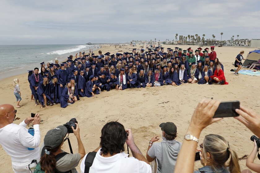 Parents take a group picture of Newport-Mesa Unified School District seniors before they participate in a graduation walk.