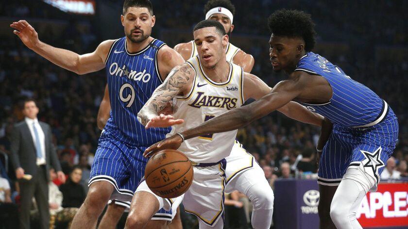 Lakers guard Lonzo Ball fights for a loose ball with Orlando Magic center Nikola Vucevic (9) and forward Jonathan Isaac at Staples Center on Sunday.
