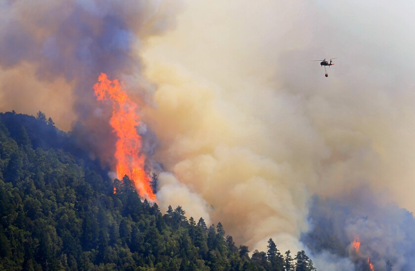 An Air National Guard helicopter moves in to make a water drop on the Lodge fire in Northern California. The fire was burning between Leggett and Laytonville in Mendocino County.
