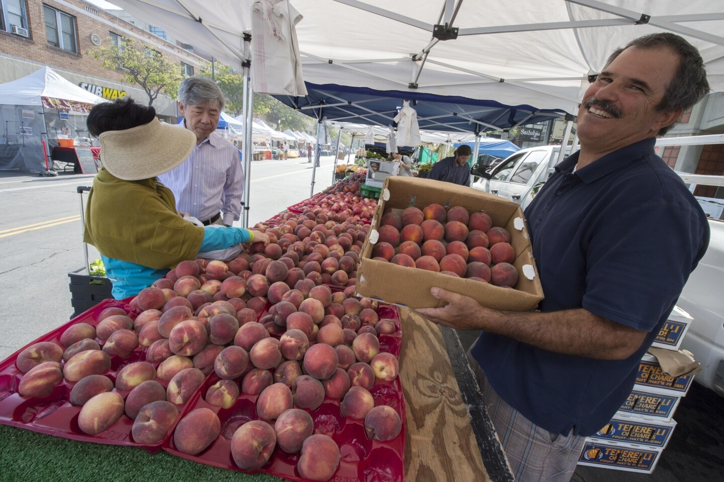 John Tenerelli holds a box with the first Summer Lady peaches of the season, which he grew in Littlerock, at the Old Pasadena farmers market.