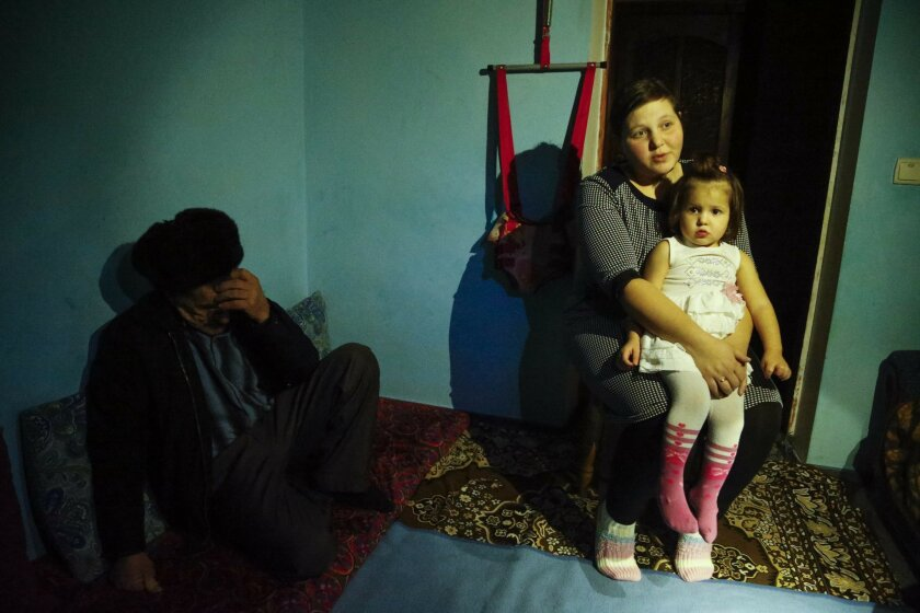 In this photo taken Sunday Jan. 24, 2016, Elnara, the wife of arrested Tatar protester Ali Asanov, sits with one of her daughters, Mumine, in her home in the village Urozhayne, Crimea. The Organization for Cooperation and Security in Europe in its report on human rights in Crimea last year said res