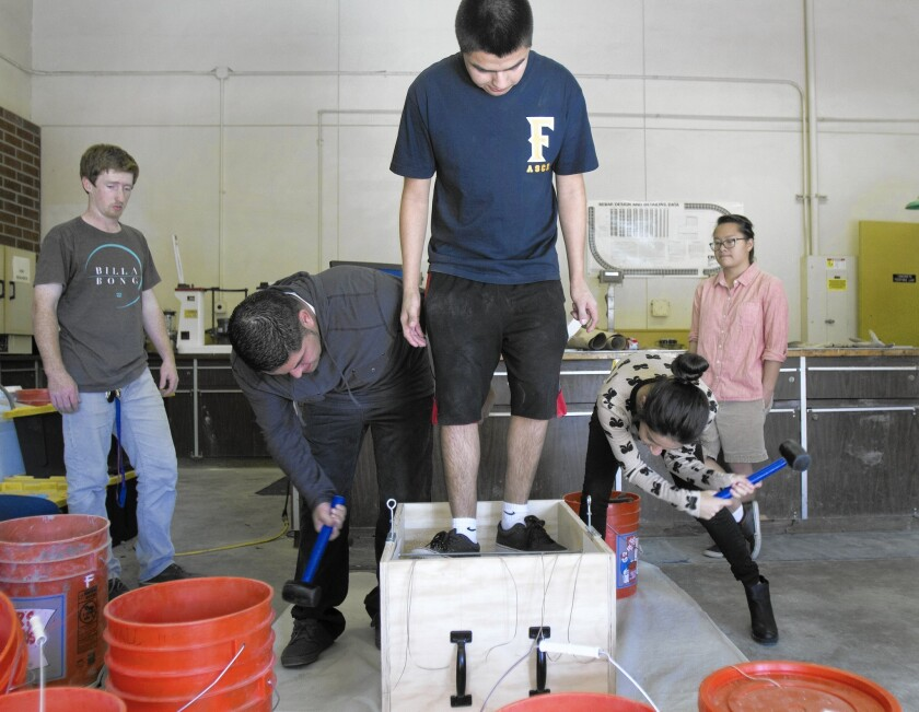 Cal State Fullerton undergraduate students John Stapleton, left, Luis Camacho, Daniel Macias, Rosalie Chavez and Alexandra San Pablo test a project for an upcoming competition in the engineering building.