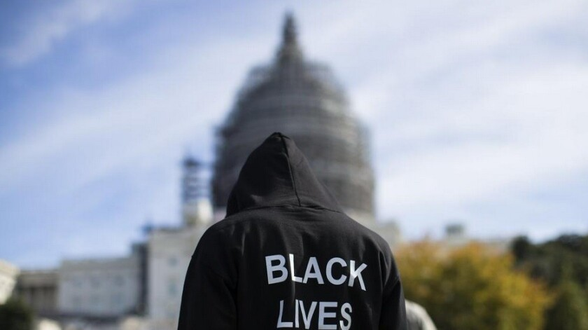 A man wearing a Black Lives Matter hoodie stands on the lawn of the Capitol building in Washington D.C.