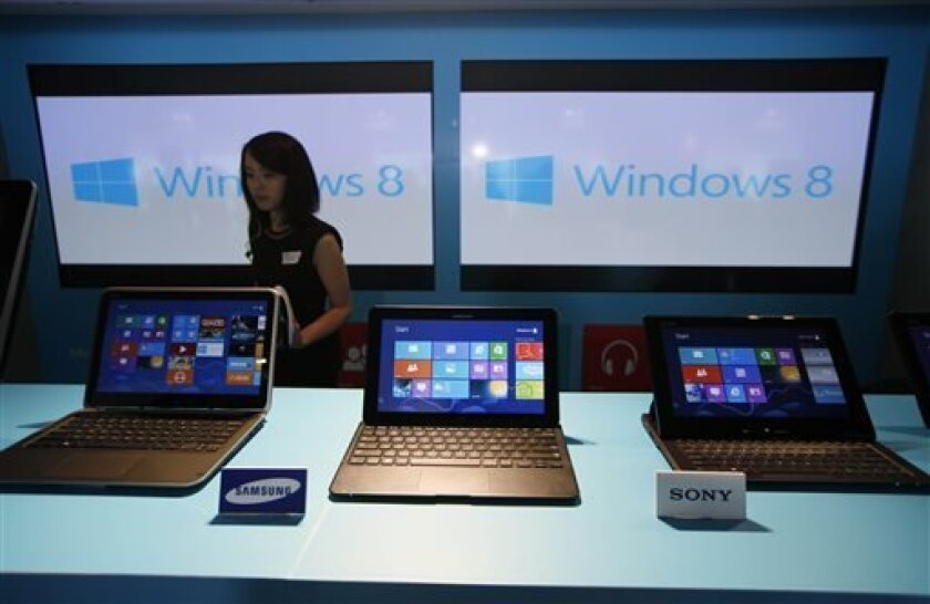 FILE - In this Friday, Oct. 26, 2012, file photo, a woman walks past laptop computers running Microsoft Windows 8 operating system during its launching ceremony in Hong Kong. Research firm IDC says PC global shipments of PCs fell 14 percent in the first three months this year. The appeal of tablets and smartphones is pulling money away from PC sales, but it also blames Microsoft's latest version of Windows, which forces users to learn new ways to control their machines. (AP Photo/Kin Cheung, Fil