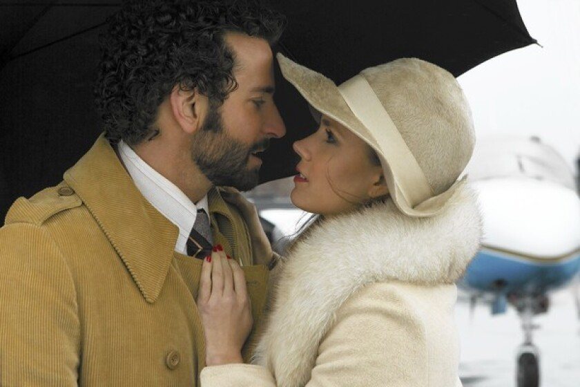 "Richie DiMaso (Bradley Cooper) and Sydney Prosser (Amy Adams) embrace each other in ""American Hustle."""