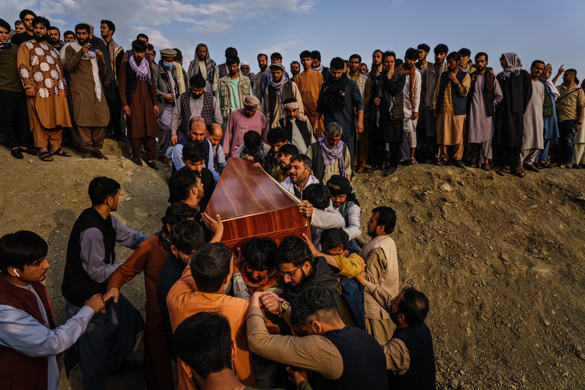 Caskets for the dead are carried toward the gravesite as relatives and friends attend a mass funeral for members of a family.