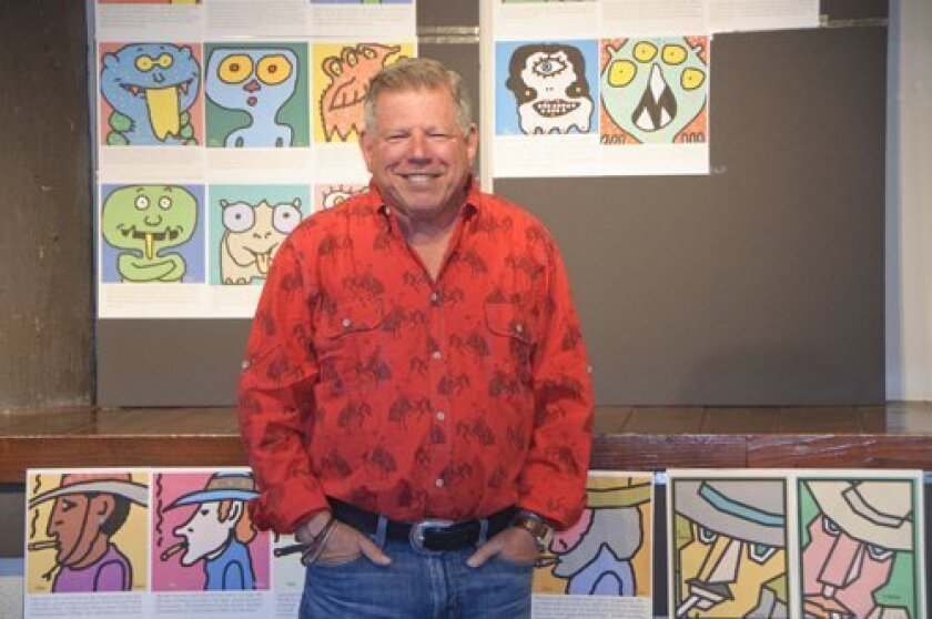 """Gary Cantor, a Del Mar resident since 1977, stands with images of his """"Cantor's characters,"""" which he sells as prints and on T-shirts."""