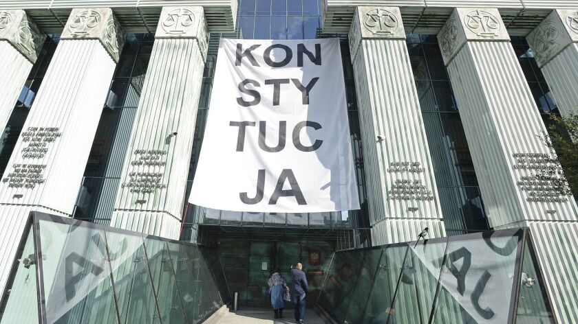 """People enter the Supreme Court in Warsaw on Oct. 11 under a banner reading """"Constitution,"""" which was hung by opponents to changes in the country's judicial law."""