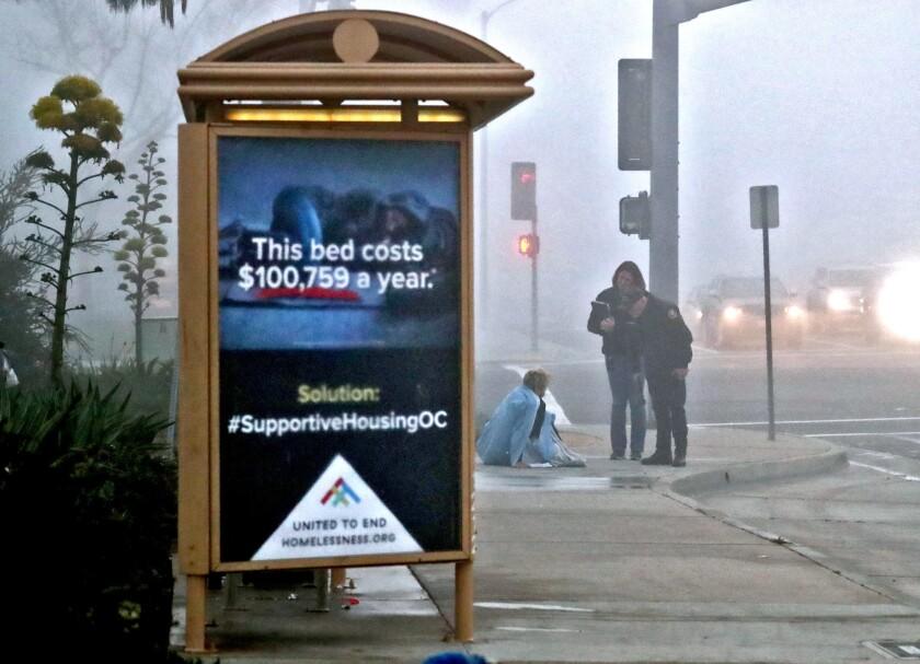 Officials speak with homeless man sleeping on sidewalk in Costa Mesa