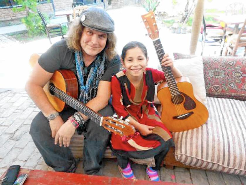 Rock musician and Cypress High alum Lanny Cordola moved to Kabul, Afghanistan, to teach street children how to play the guitar.