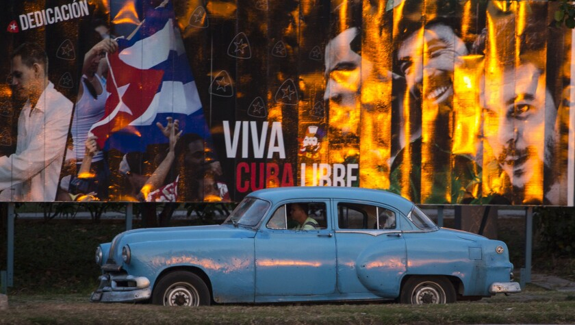 """A cabdriver in a classic American car passes a billboard that reads in Spanish, """"Long live free Cuba,"""" in Havana on March 14."""