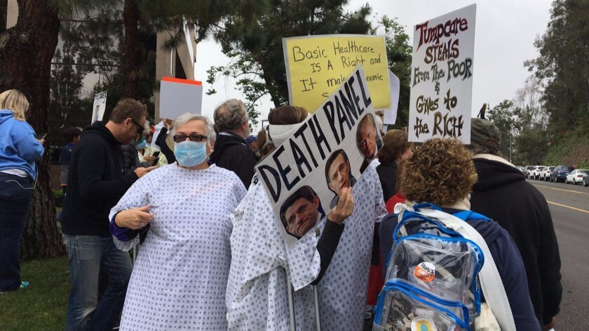 Protesters don hospital gowns and surgical masks outside Rep. Darrell Issa's Vista office to protest his vote on the GOP healthcare bill.