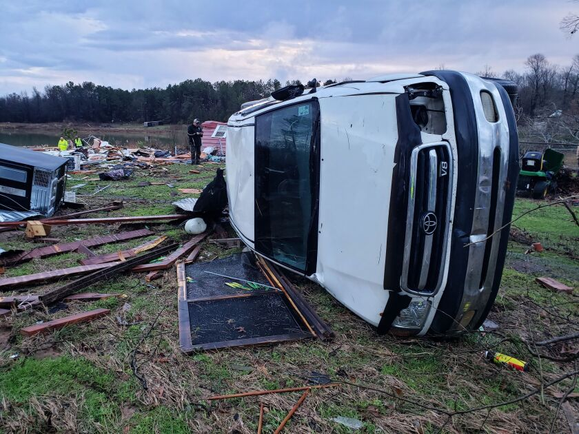 A white truck turned on its side amid damage from severe weather in Bossier Parish, Louisiana