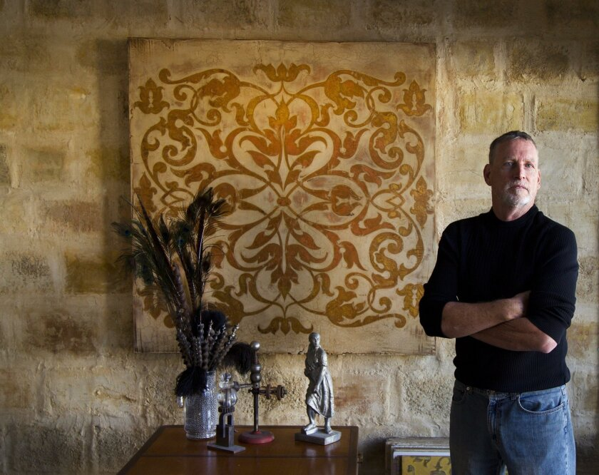 Self-taught artist Thomas Alan Byrne in front of a faux stone wall he created in his studio. For more than 30 years, Byrne has made hand-painted designs, faux finishes, trompe l'oeil artwork and murals for homes around the country.