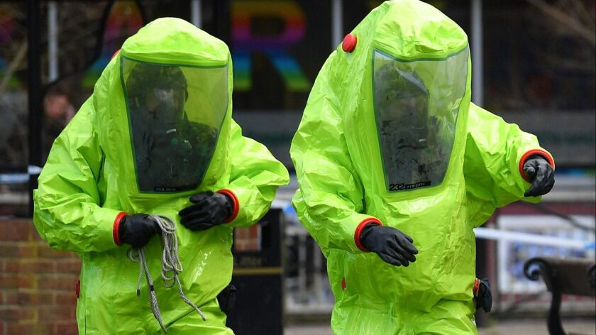 Members of the emergency services wear green biohazard suits as the investigate area when a former Russian spy and his daughter were found last month.