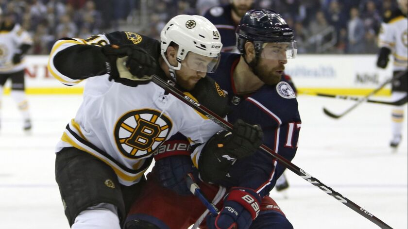 Boston Bruins defenseman Matt Grzelcyk, left, and Columbus Blue Jackets forward Brandon Dubinsky chase after a loose puck during Game 3 of the NHL Eastern Conference semifinals on April 30.