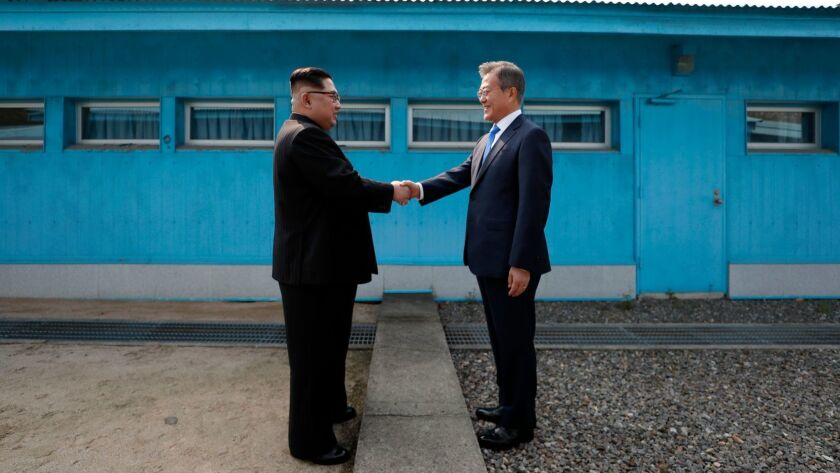 North Korea's leader Kim Jong Un, left, shakes hands with South Korea's President Moon Jae-in at the Military Demarcation Line that divides their countries ahead of their summit at the truce village of Panmunjom.
