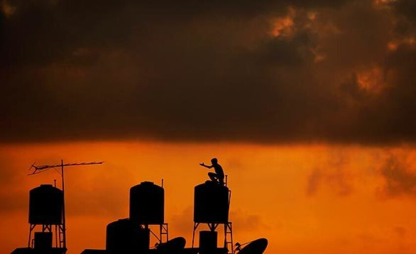 A Palestinian youth checks a rooftop water tank as the sun sets on the outskirts of the West Bank city of Ramallah.